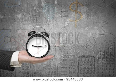 Hand Holding Alarm Clock With Doodles Concrete Wall