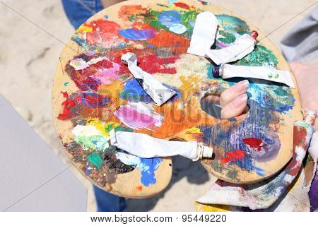 Female hands holding tubes of paint on palette close up