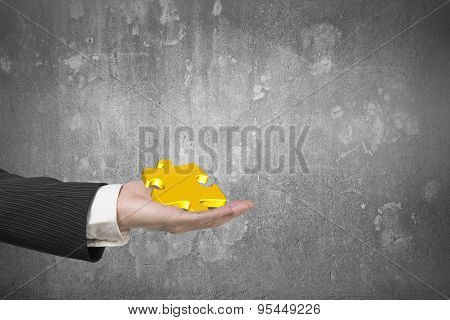 Male Hand Holding One 3D Gold Jigsaw Puzzle Piece