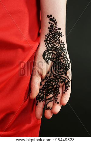Image of henna on female hand on dark background