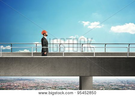 smiley man in formal wear and orange hard hat walking on concrete bridge