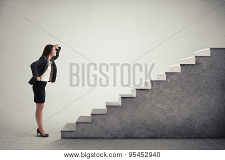serious woman looking up at top of concrete stairway over light grey background