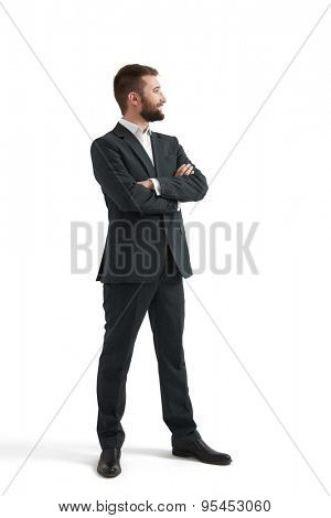 full-length portrait of successful businessman in formal wear with folded hands looking at something. isolated on white background