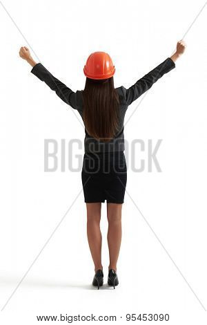 back view of happy businesswoman in orange hardhat with raising her hands up. isolated on white background