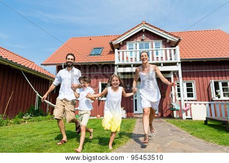 Family having fun with their new home or house running through the front yard