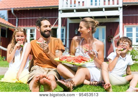 Family sitting in grass in front of house eating water melon to refresh in summer