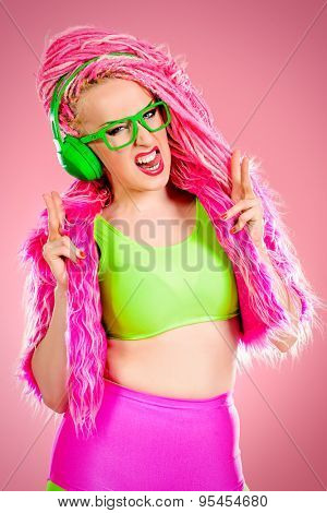 Trendy DJ party girl in bright clothes, headphones and with bright pink dreadlocks. Disco, party. Show business. Bright fashion.