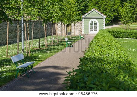 Walkway In Garden Between Benches And Green Fence