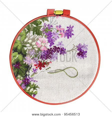 Handmade cross-stitch with floral pattern on canvas. Isolated on white background