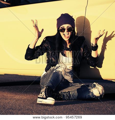 Angry fashion punk woman sitting by her car