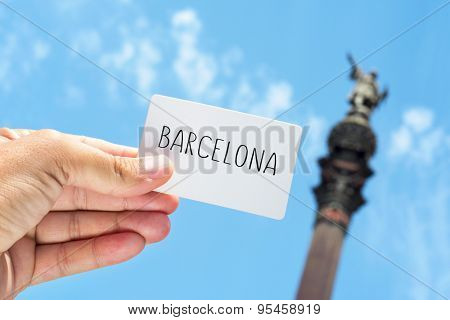 closeup of the hand of a young man showing a signboard with the text Barcelona, with the famous Columbus Monument in the background in Barcelona, Spain