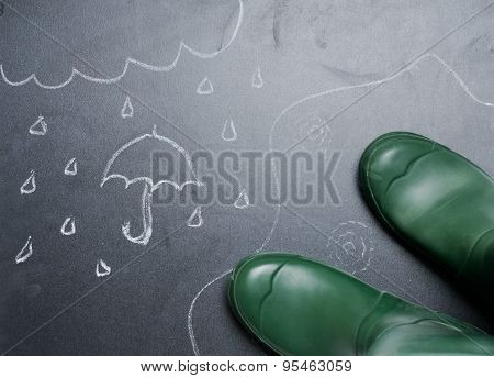 Rubber Boots With Drawing Of Rainy Day On The Blackboard From The Top View