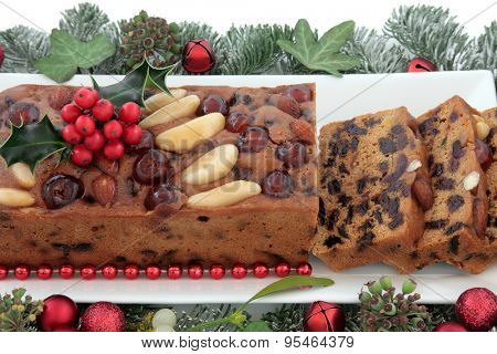 Genoa cake and slices with holly, red bauble christmas decorations and winter greenery over white background.