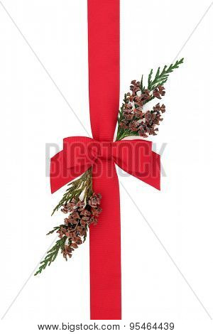 Red ribbon and bow with cedar cypress leaf sprigs over white background.