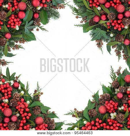 Christmas background border with red bauble decorations, holly, mistletoe, ivy, pine cones and traditional winter greenery over white.