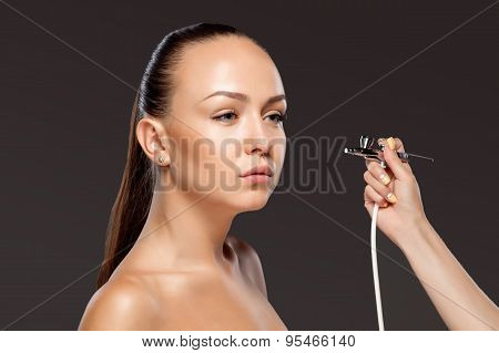 visagist making makeup for model with aerograph