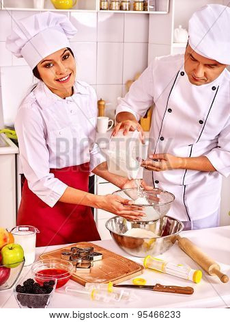 Two people  woman and man in chef hat cooking dough .