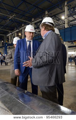 ST. PETERSBURG, RUSSIA - JUNE 30, 2015: Governor of Leningrad oblast Alexander Drozdenko (blue suit) in Megapolis plant owned by Amira Group. It's Russia's largest plant producing the lighting poles