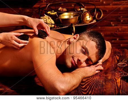Man  having hot stones spa treatment.