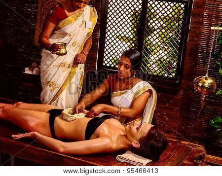 Young woman having stomach oil Ayurveda spa treatment.