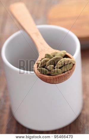 Cardamom in a wooden spoon