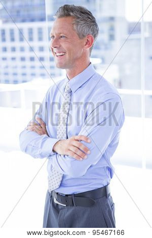 A smiling businessman looking away in the office