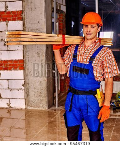 Happy man in builder uniform carry wooden boards indoor.