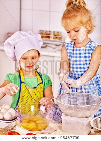 Kids with rolling-pin dough at kitchen. Children smeared into flour.
