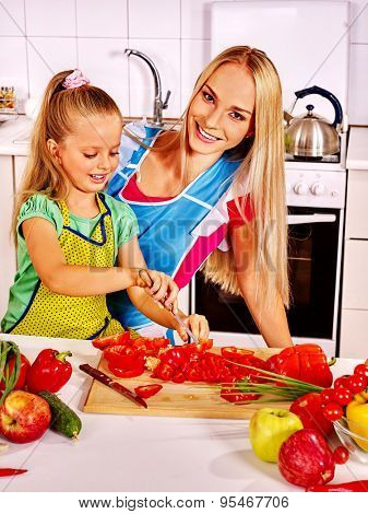 Mother and daughter cooking vegetable food at kitchen.