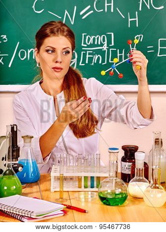 Chemistry teacher with test-tube preparing lesson at classroom.