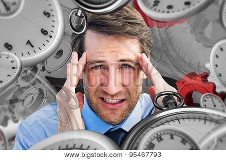 Young businessman with severe headache against grey background