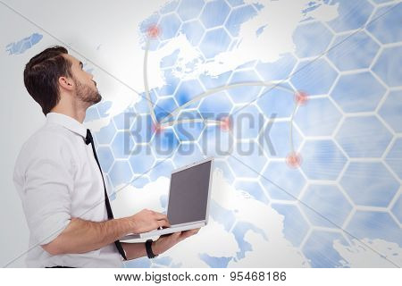 Sophisticated businessman standing using a laptop against world map