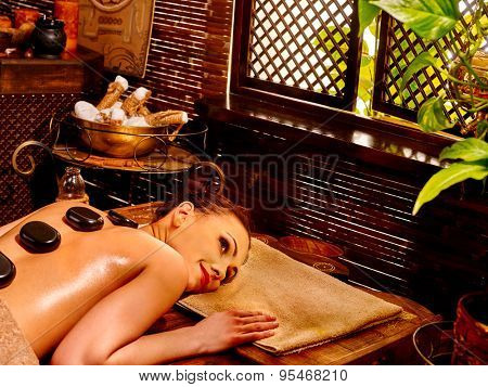 Young woman having Ayurveda stone on back massage.