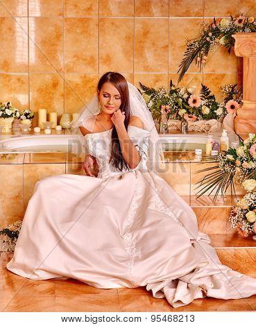 Woman wearing wedding dress relaxing at spa.