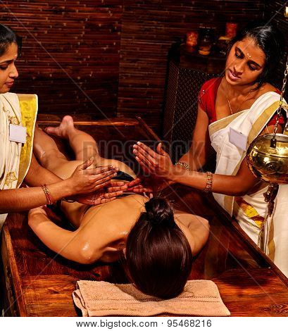 Young woman having oil Ayurveda spa treatment. Two Indian masseuses.