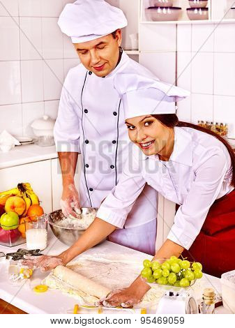 Happy woman and man in chef hat cooking dough .Girl looking at camera.