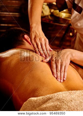 Man  having oil Ayurveda spa treatment. Male back close up.