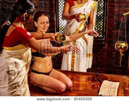 Young woman having oil Ayurveda by two masseuse spa treatment.
