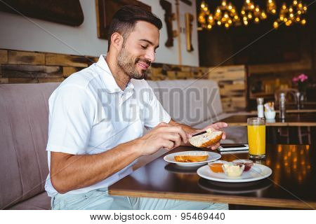 Young man spreading butter on a toast at the cafe