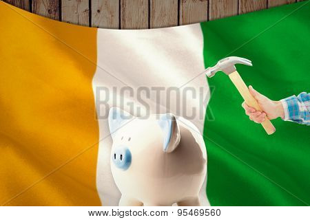 hand holding hammer against ivory coast national flag
