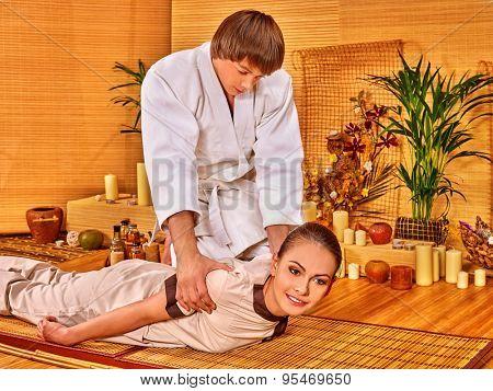 Man in white uniform making bamboo massage of beautiful woman.
