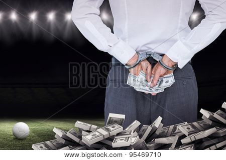 Businessman in handcuffs holding bribe against football pitch at night with ball and lights