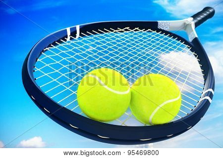 Two tennis balls and racket on blue clouds sky background outdoor.