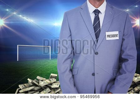Businessman with badge against pile of dollars