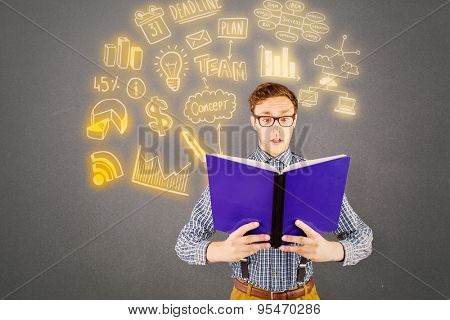 Geeky businessman reading a book against grey background