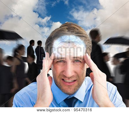 Young businessman with severe headache against blue sky