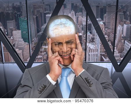 Stressed businessman putting his fingers on his temples against room with large window looking on city