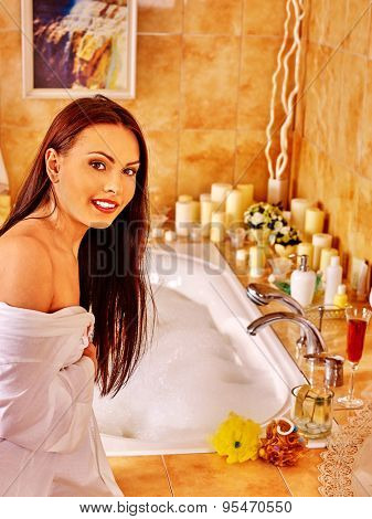 Woman relaxing at home luxury bath. Girl next to edge of bath.