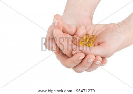 Woman's hands holding vitamin D pills on white