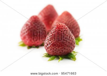 Four very ripe strawberries pointed upwards, isolated on white. shallow depth of field.